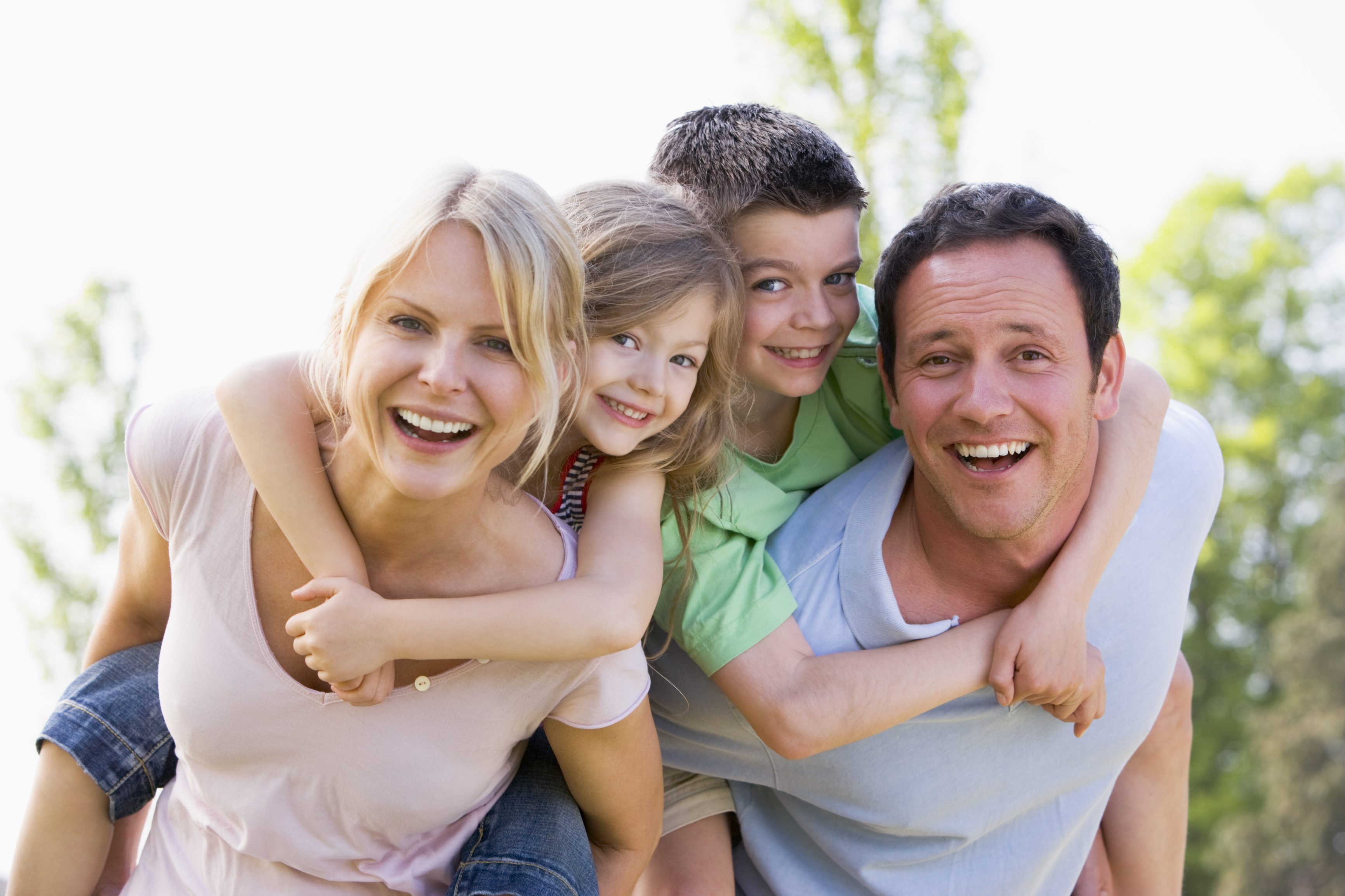 couple-giving-two-children-piggyback-rides-smiling