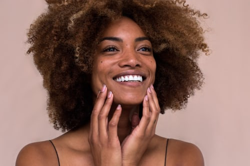 young woman smiling and touching her face